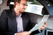 Elegant man reading papers in luxury car