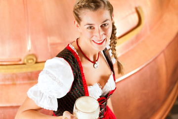 Frau in Tracht mit Bier Glas in Brauerei
