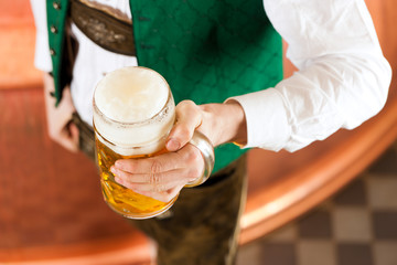 Mann in Tracht mit Bier Glas in Brauerei