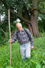 An elderly man with a backpack tourist goes into the thickets