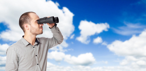 Business man with binoculars looking to the future or looking fo