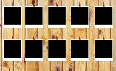 set of ten old blank polaroids frames lying on a wood surface