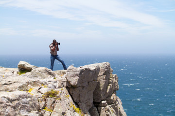 african photographer taking photos on cliff