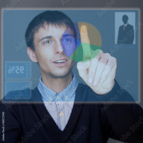 Portrait of adult business man pressing a touchscreen button whi