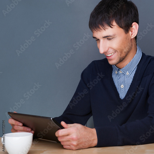 Closeup of a young smiling business man sitting at his office ag