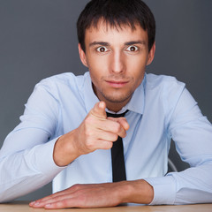 Portrait of aconfident young business man in suit pointing at yo