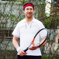 Mature man playing tennis at his backyard of his house