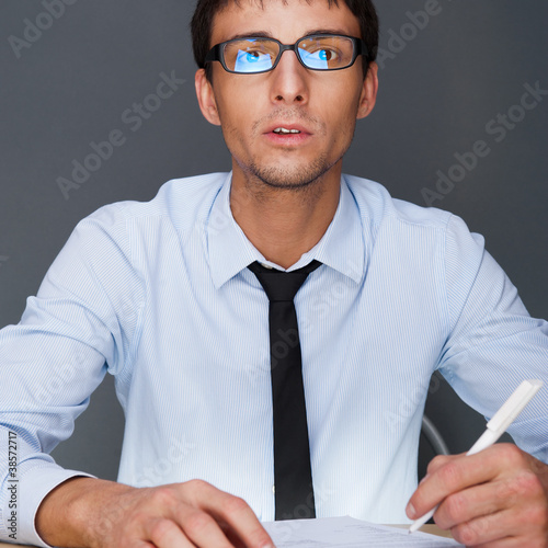 Portrait of an adult business man sitting in the office and sign
