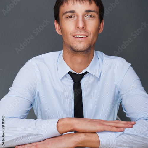 Portrait of young business man on a desk. He is sitting at his n