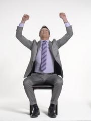 Joven ejecutivo sentado contento y celebrando.
