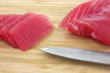 Sliced yellowfin tuna on cutting board poster