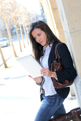 Woman leaning on wall in town with electronic tablet