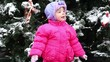 Little girl stands and look toward in front of Christmas tree