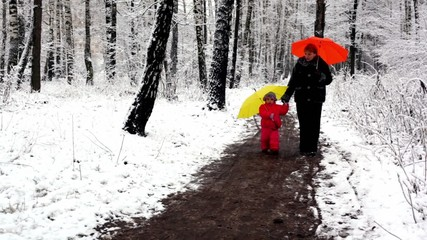 Woman and girl walking in snow-covered park holding hands