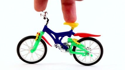 Fingers on toy bike, rotates handlebars, then ride away