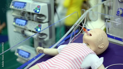 Dummy of child with tube in mouth at medical box