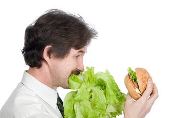 Man eats salad and looks at hamburger