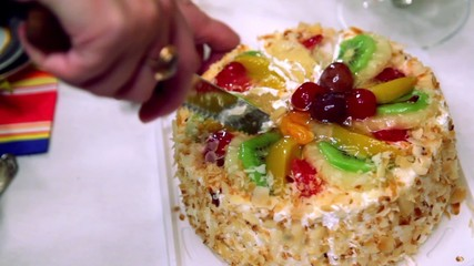 Hands severs sweet fruit cake by knife