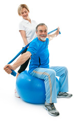 Senior man doing fitness exercise with help of trainer