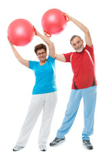 Senior couple doing fitness exercise with a ball in gym