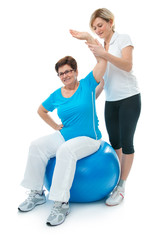 Senior woman doing fitness exercise with help of trainer in gym