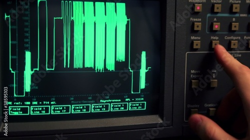 Hand push buttons and rotates knob on oscilloscope