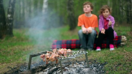 Boy and girl sit on log and watch at fresh meat on embers