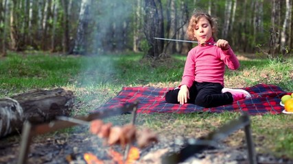 Little girl, sit on grass cover by plaid and eats kebab
