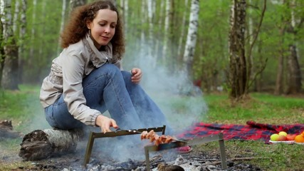 Woman sit and rotate skewer with fresh meat under embers