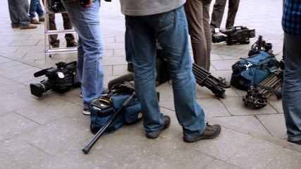 Television equipment lay on ground near operators legs