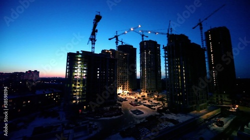 Night shift at construction site in foreground of cityscape