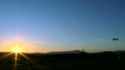 Flugzeug landet vor untergehender Sonne