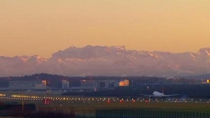 Flugzeug landet im Abendlicht vor Alpenkulisse