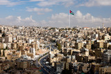 view of the city of Amman with Jordanian flags