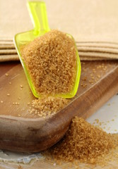 Cane sugar in spoon on a  wooden board