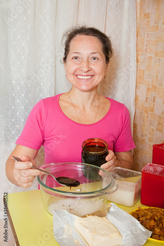 woman adds honey into dish with suga