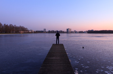 Man looking at the ice of a frozen lake near a city