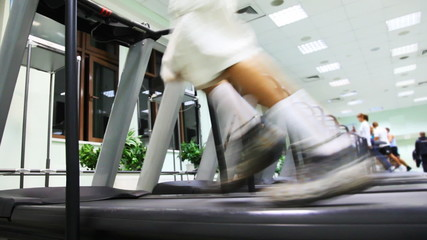 legs man quickly run on one of many treadmill in gym