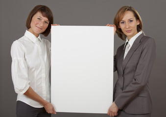 two women holding blank board