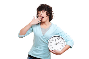 young woman holding clock and yawning