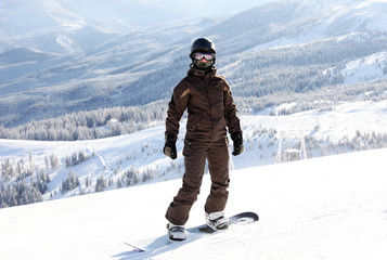 Female snowboarder on mountain slope