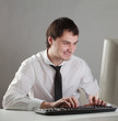 young man at the computer happy, looking at the monitor