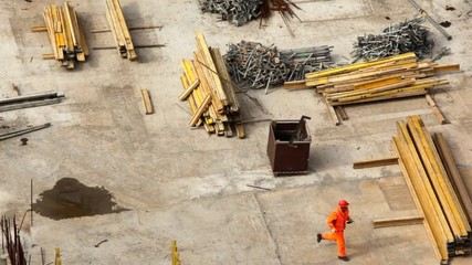 worker runs on building site among materials