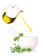 mortar with fresh herbs and pouring oil