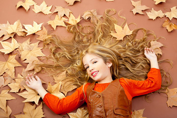 autumn fall little blond girl on dried tree leaves