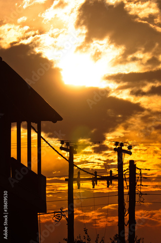 Silhouette of a high voltage post and a house