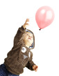 portrait of funny kid trying to hold a pink balloon over white b
