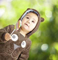 portrait of a handsome kid wearing a brown bear sweatshirt holdi