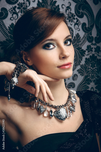 Portrait of pretty young woman with beads and bangle