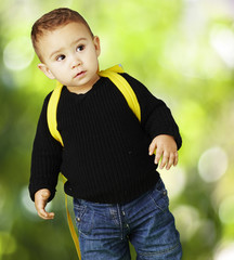 portrait of adorable kid carrying yellow backpack against a natu